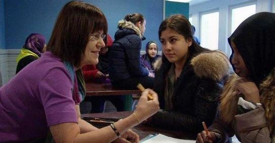 Stillbild från filmen som visar Gunilla Lundgren och två elever som sitter och skriver.