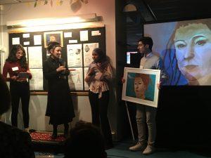 Elever från Enbacksskolan i Tensta överlämnar ett porträtt till Olga Tokarzcuk på Rinkeby bibliotek.
