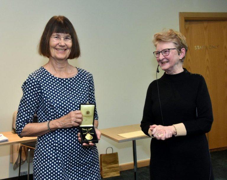Gunilla Lundgren ler och tar emot en medalj. Till höger om henne står Marianne af Malmborg som är ordförande i Kungliga Sällskapet Pro Patria.