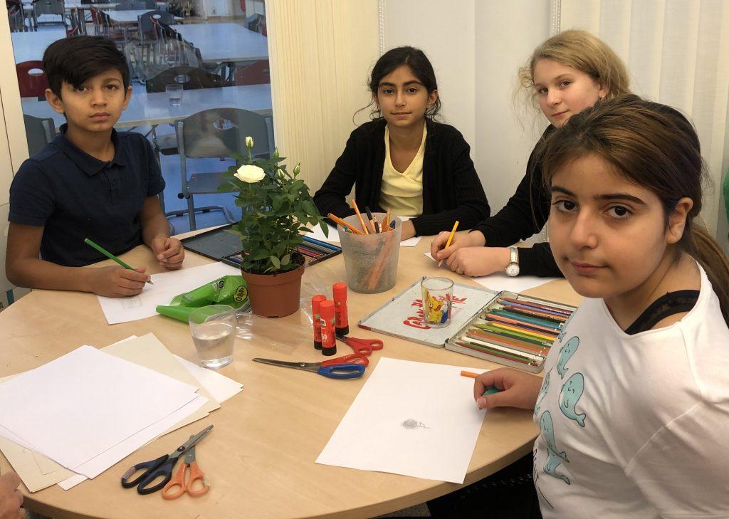 Fyra elever sitter och ritar vid ett bord.