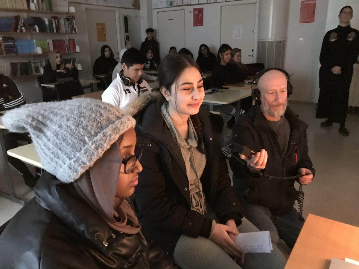 Två elever och en radioreporter i klassrummet. I bakgrunden syns fler elever..