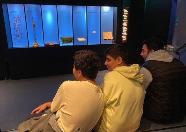 Tre pojkar som sitter och tittar på en monter med olika föremål.