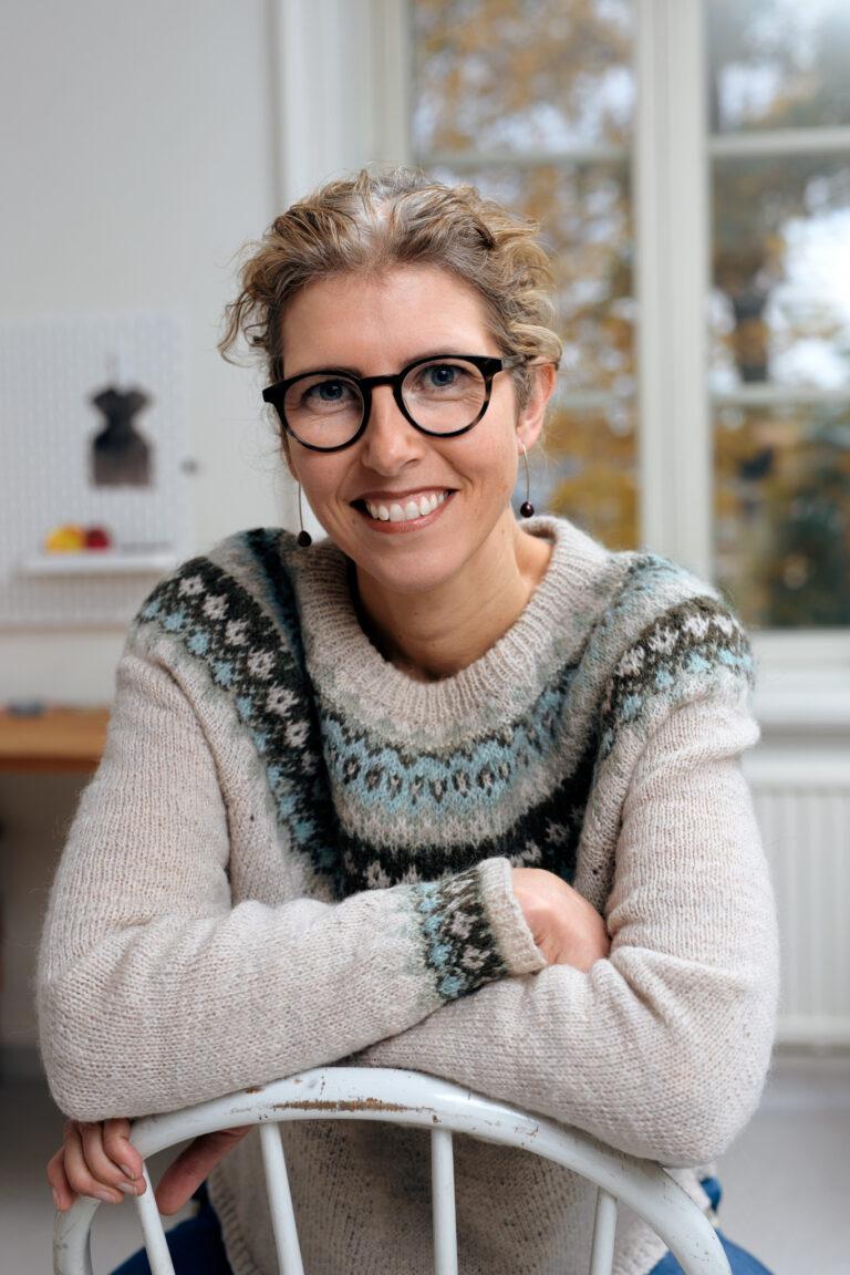 Emma Virke ler och lutar armarna mot ryggstödet på en stol. FOTO: Stefan Tell